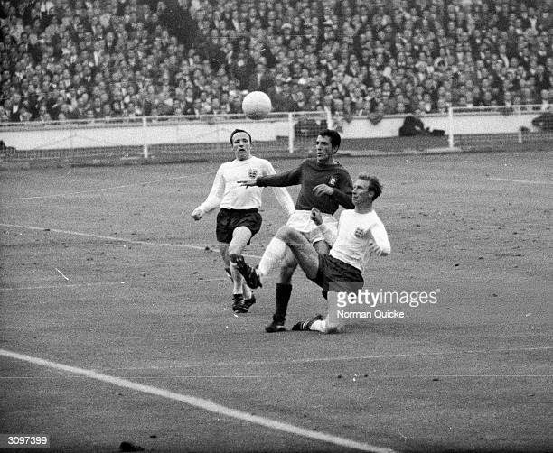 English footballers Jack Charlton and Nobby Stiles challenging a Portuguese player during the World Cup semifinal at Wembley