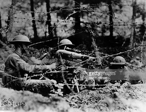 American soldiers manning a French '37' a onepounder in firing position behind barbed wire in a second line trench at Dieffmatten in Alsace