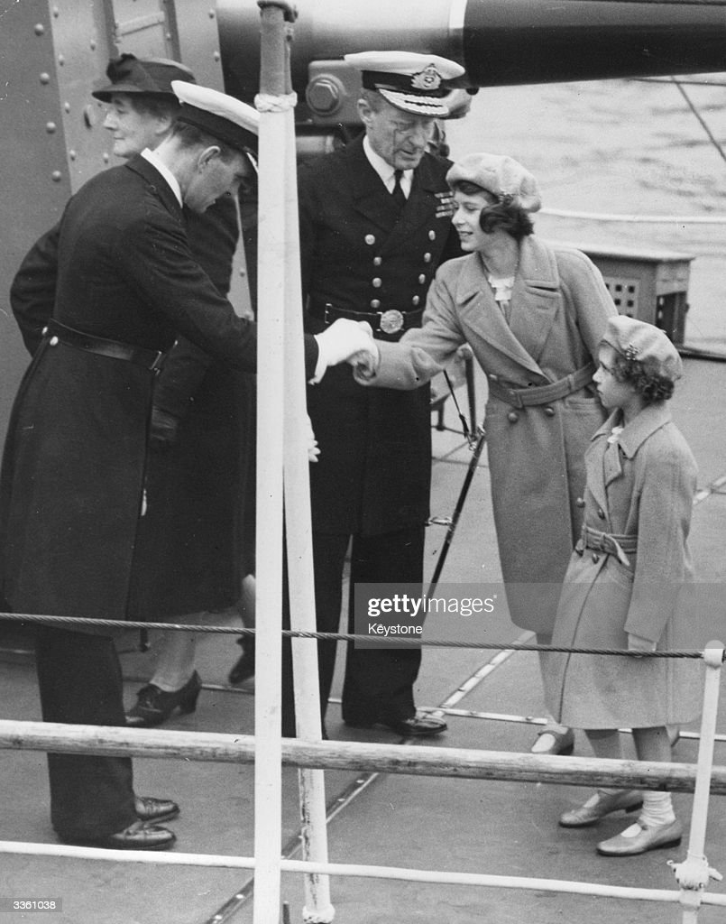 Princess Elizabeth (later Queen Elizabeth II) and Princess Margaret (1930 - 2002) being greeted on their arrival on board the warship HMS Kempenfeld at Portsmouth.