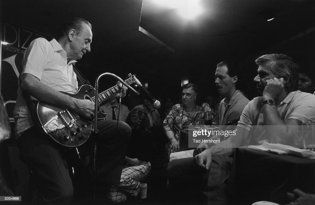 American pop and jazz musician Les Paul plays an electric guitar on stage in close proximity to an audience seated at the front row tables of the nightclub club Fat Tuesdays, New York City.