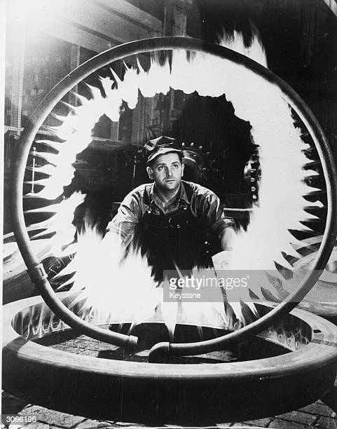 A workman at the locomotive shop of the General Electric Company in Eric Pennsylvania tests a gas ring used for heating the wheels of dieselelectric...