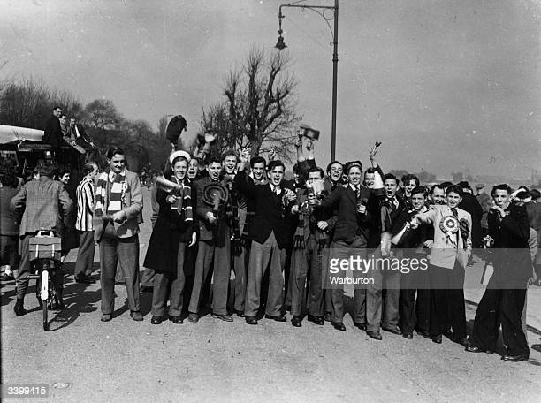 Supporters of Portsmouth FC find the time to watch the Oxford and Cambridge Boat race on their way to Highbury for Portsmouth's match against...