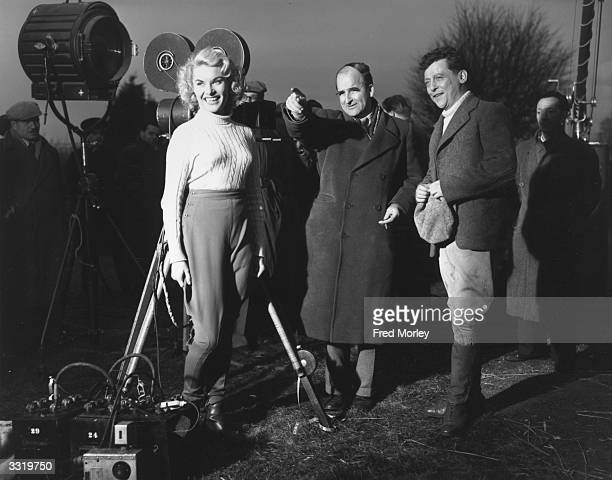 Director Frank Launder giving instructions to cast members Belinda Lee and Michael Ripper during the filming of 'The Belles Of St Trinians' on...