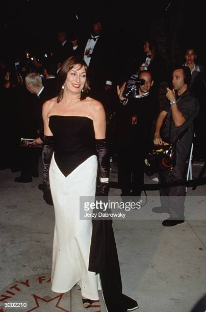 Fulllength image of American actor Anjelica Huston posing in a strapless dress with a black bodice and a white skirt long black gloves and a black...
