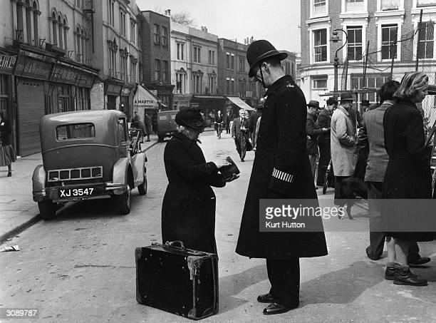 A policeman helps an old lady in Portobello Road market west London Original Publication Picture Post 5309 All London pub1951