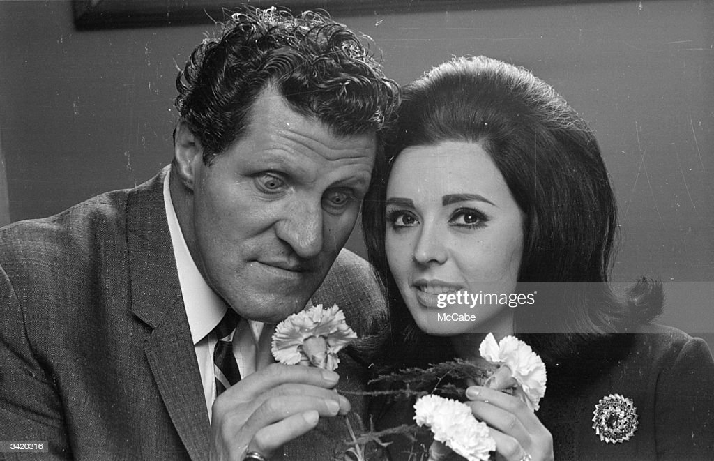 British comic Tommy Cooper (1922 - 1984) investigating a bunch of carnations with pop singer Susan Maughan, most famous for her hit 'Bobby's Girl'.