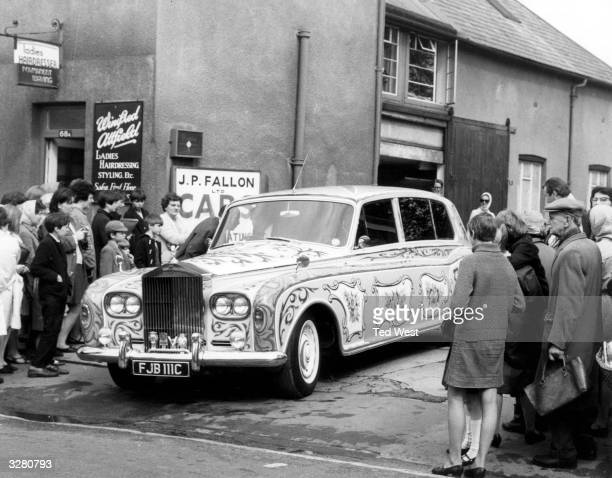 A crowd gathers to stare at a luridly painted Rolls Royce leaving the coachbuilders after a respray The car belonging to Beatle John Lennon was a...