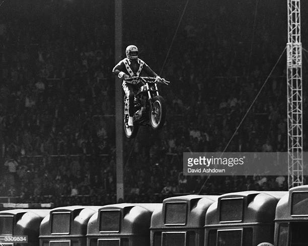 Stuntman Evel Knievel jumping 140 feet at 90 mph over 13 buses at Wembley stadium Unfortuneately he crashed on landing damaging his spine