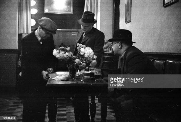Men playing shoveha'penny in the bar of an English public house Original Publication Picture Post 46 Pubs pub 1938