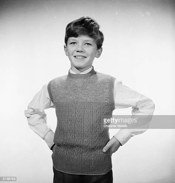 A young schoolboy modelling a woollen sleeveless crew neck sweater
