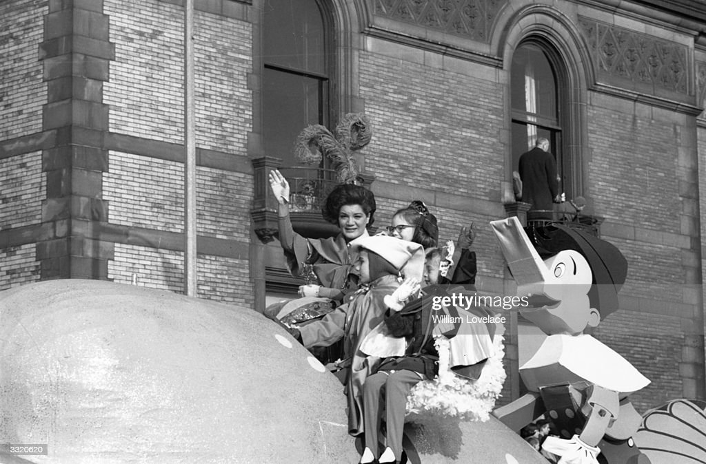 A family group on a float in a Thanksgiving Day parade in New York with a model of Pinocchio riding pillion