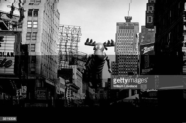 An balloon shaped like Bullwinkle of 'Rocky and Bullwinkle' fame floats above the Thanksgiving Day Parade in New York past cinemas and theatres as it...