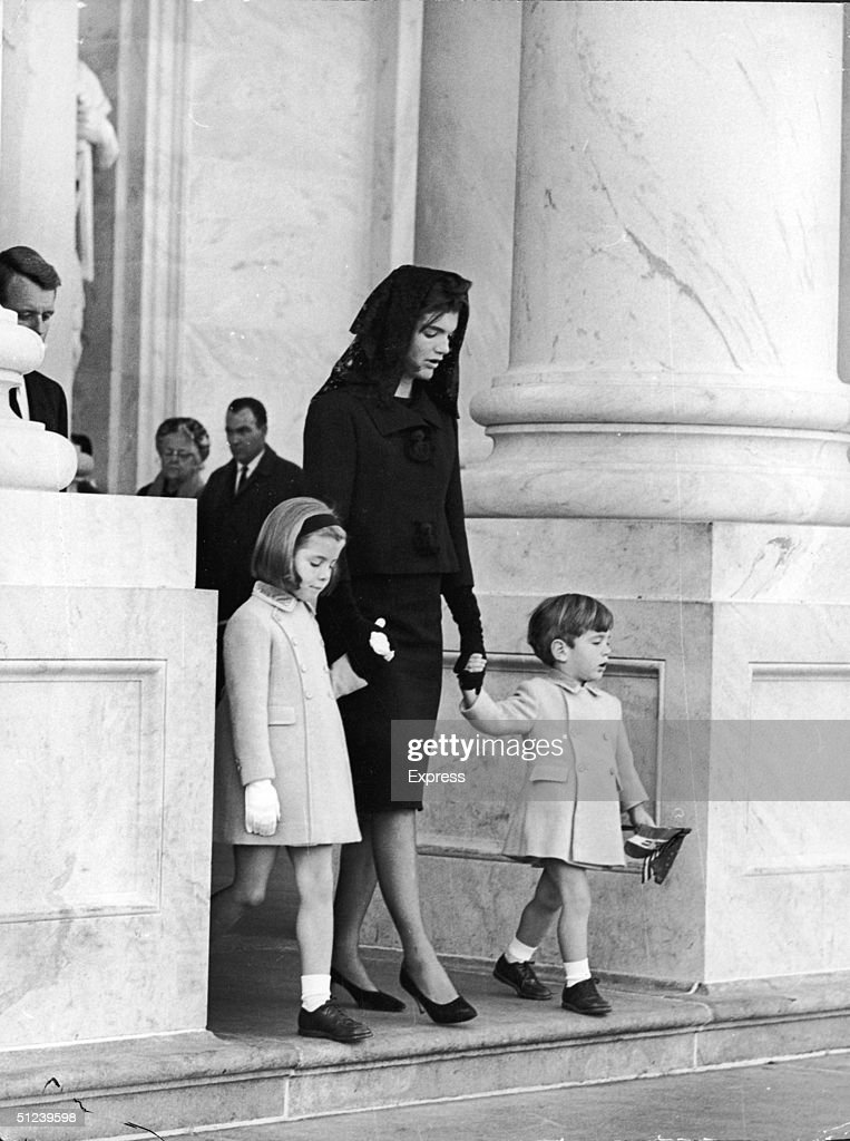 26th November 1963 First Lady Jacqueline Kennedy holds the hands of her two children John Jr and Caroline as they leave the White House to attend the...