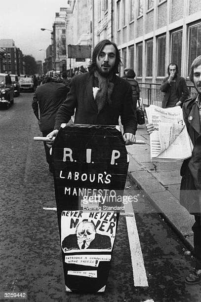 An unemployed person makes his protest by wheeling a coffin denoting the Labour Party's manifesto as deceased through the streets