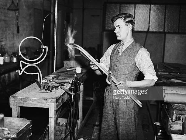 A craftsman uses a blowtorch to create neon signs for the King's coronation at a factory in Earlsfield London