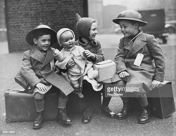 Three young evacuees sit on their suitcases ready for their journey away from the danger of the city