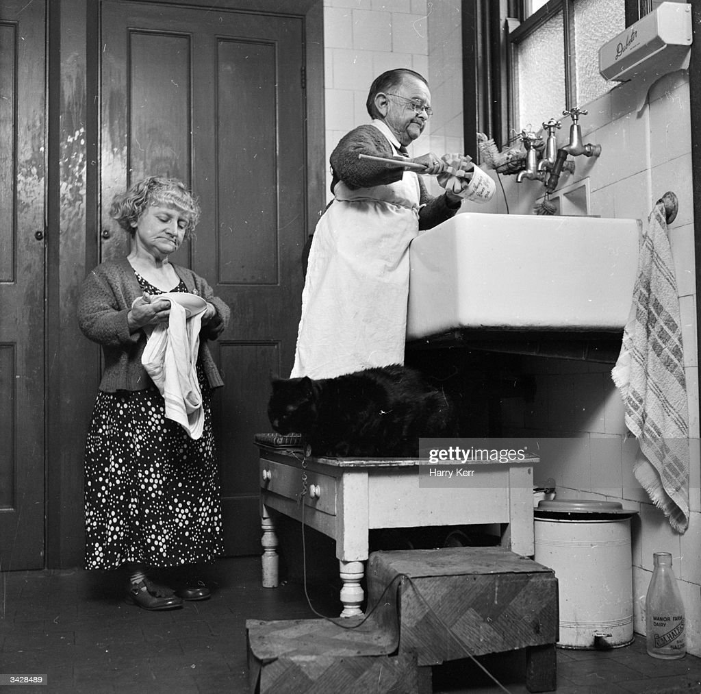 Henry Behrens, the smallest man in the world stands on a table to do the washing up in the kitchen of his Worthing home. Measuring only 30 inches high, Mr Behrens has made a living by travelling the world with Burton Lester's midget troupe and is married to 40-inch high Emmie.