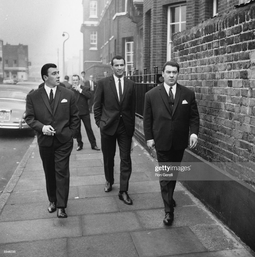 London gangsters Ronnie and Reggie Kray walking along an East End street, London.
