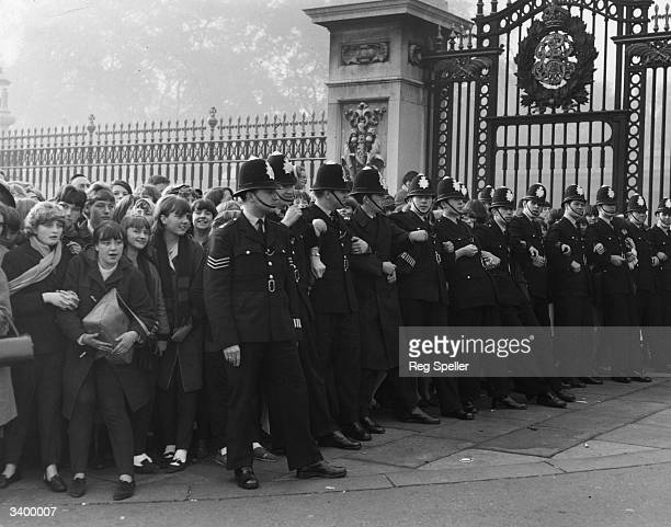 Policemen holding back crowds of young fans of pop group The Beatles outside Buckingham Palace London where the band were awarded their MBE's by...