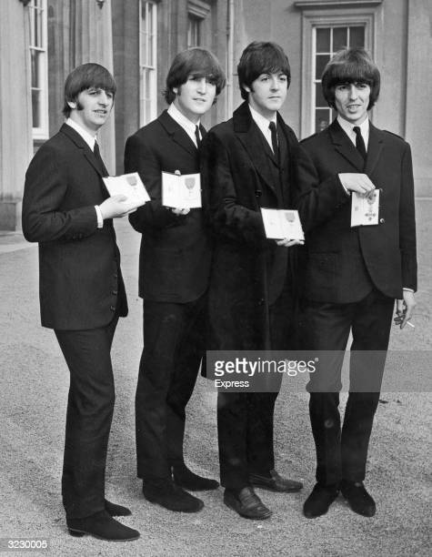 Ringo Starr John Lennon Paul McCartney and George Harrison display their Member of the Order of the British Empire awards from Queen Elizabeth...