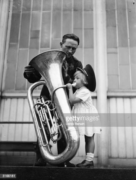 A little girl is dwarfed by a giant tuba at the National Brass Band Contest at Crystal Palace London