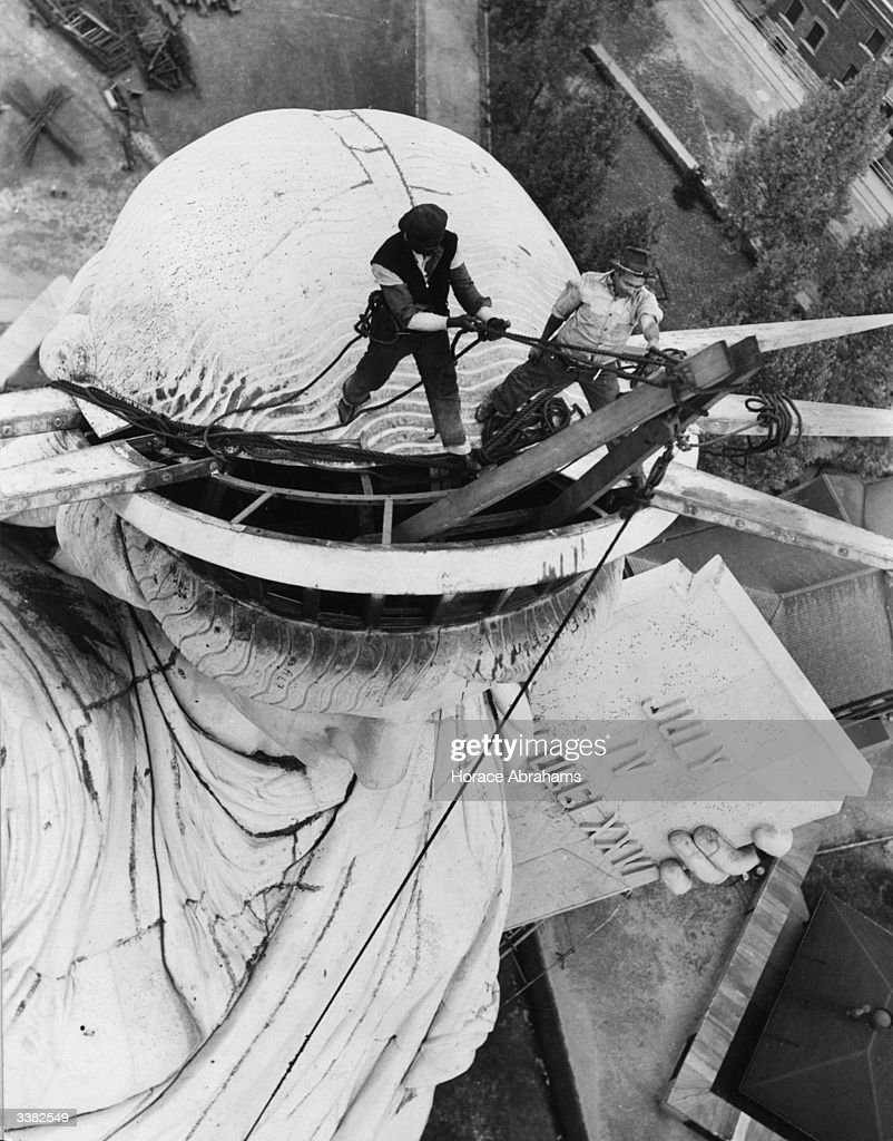 Steeplejacks removing the spiked crown from the head of the Statue of Liberty, New York, for renovation work before the World's Fair.