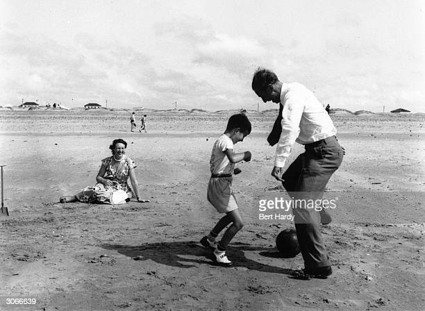 Footballer Stanley Matthews playing with his family on Blackpool sands where he lives First footballer to be awarded the CBE to be knighted and first...