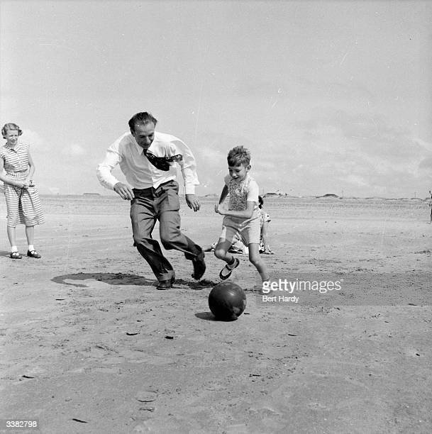 The country's most famous football player Stanley Matthews of Blackpool FC plays with his son Stanley Junior on the beach Original Publication...