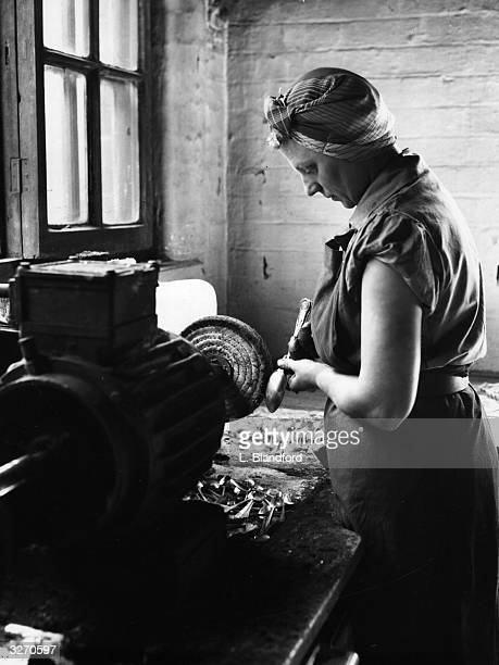 An employee at a factory in Sheffield polishes a spoon on a wheel one of a sequence of abrasive operations in the cutlerymaking process