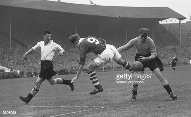 Derby County goalkeeper Vic Woodley tries to catch the ball as Charlton Athletic centre forward Bert Turner forces a corner off Leon Leuty Turner...