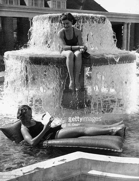 Two young women have found a cool method of reading and relaxing in a fountain at an openair swimming pool in Finchley London