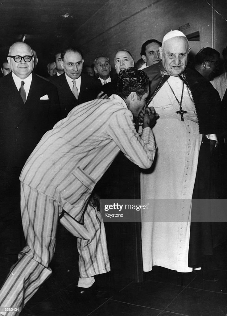 Angelo Giuseppe Roncali, Pope John XXIII (1881 - 1963) being kissed by an inmate during a visit to the Regina Coeli prison in Rome.