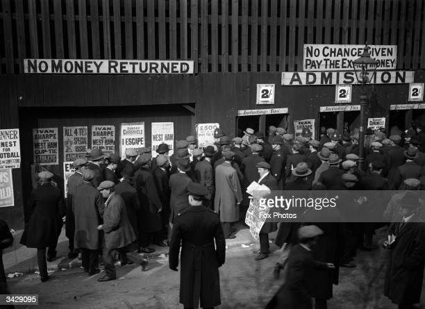 Football fans queuing to get into a West Ham versus Arsenal Cup Tie match