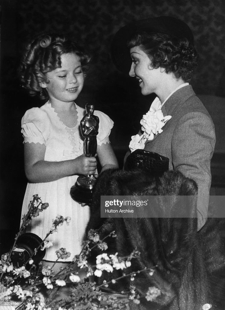 American actor <a gi-track='captionPersonalityLinkClicked' href=/galleries/search?phrase=Shirley+Temple&family=editorial&specificpeople=69996 ng-click='$event.stopPropagation()'>Shirley Temple</a> presents the Best Actress Oscar to French-born actor <a gi-track='captionPersonalityLinkClicked' href=/galleries/search?phrase=Claudette+Colbert&family=editorial&specificpeople=93238 ng-click='$event.stopPropagation()'>Claudette Colbert</a> (1903 - 1996) for her role in director Frank Capra's film, 'It Happened One Night', Los Angeles, California. Colbert holds a fur coat over her arm, preparing to travel to New York City.