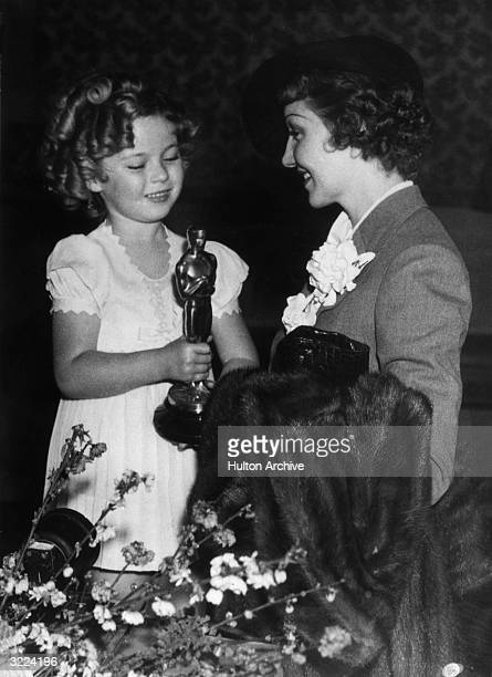 American actor Shirley Temple presents the Best Actress Oscar to Frenchborn actor Claudette Colbert for her role in director Frank Capra's film 'It...