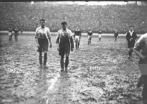 Two Preston North End players leave the pitch at halftime covered in mud during a match against Charlton Athletic at 'The Valley'
