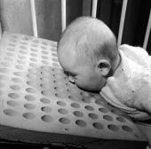 A baby with a foam rubber pillow invented to prevent small children suffocating in their cots by Roland Ward of the Public Health Department of Eton...