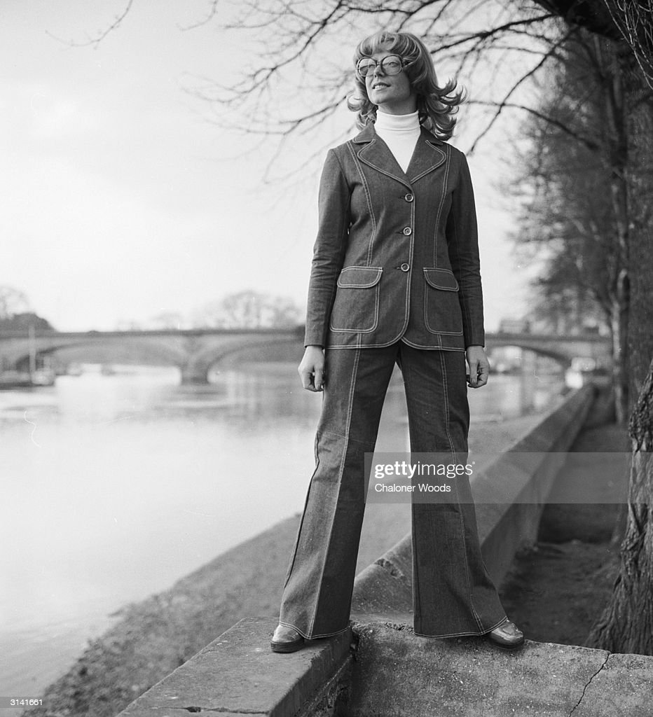 A woman stands confidently on the banks of a river, sporting a flared denim suit over a white polo-neck jumper.