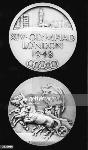 The two sides of a gold medal made for the 14th Olympic Games which are to be held in London The medals are made from oxidised silver instead of the...
