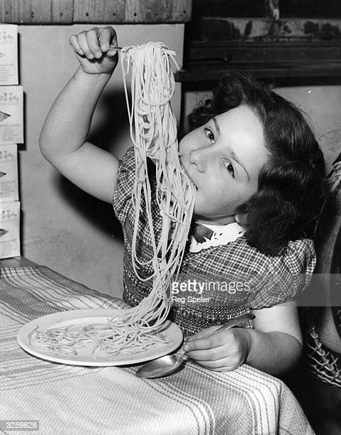 A young girl enjoying a plate of her father's spaghetti made at Messrs L Ugo Ltd London The factory specialises in all types of pasta and rivals the...