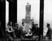 Construction workers take a lunch break with the 300 ft high chimney of Battersea Power station which is nearing completion in the background