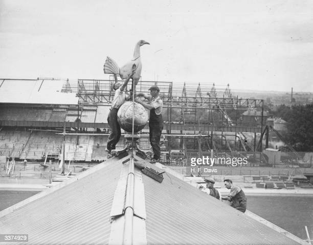 Workmen repairing the 'Hotspur' on the old stand at Tottenham Hotspur FC ground In the background a new stand is being built