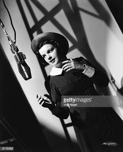 Judy Garland wearing a straw sailor hat and a long sleeved dress with white collar and cuffs gets ready to sing