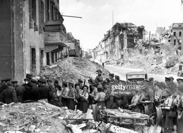 Allied soldiers queuing outside the devastated German Chancellery to see the remains of Adolf Hitler's underground shelter where he is reputed to...