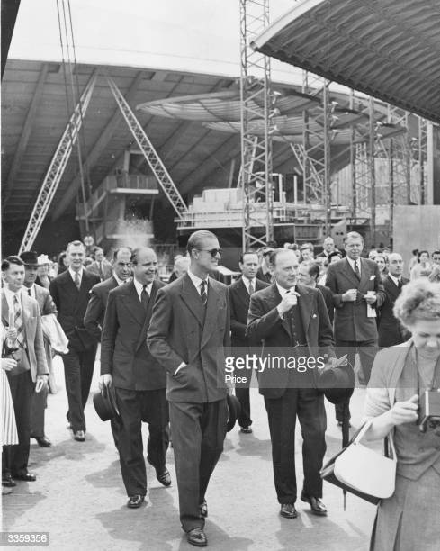 The Duke of Edinburgh wearing dark glasses is conducted on a tour of the Festival of Britain South Bank Exhibition in London On the left behind the...
