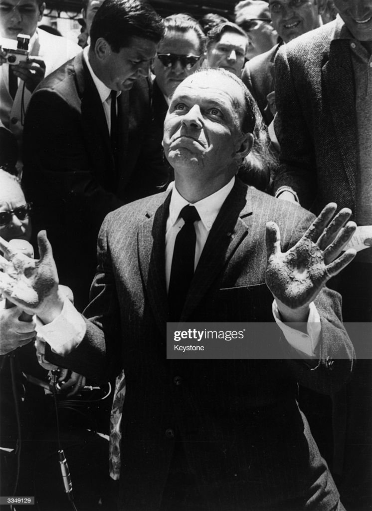 American actor and singer Frank Sinatra with his hands covered in cement after making an imprint at Grauman's Chinese Theatre Hollywood