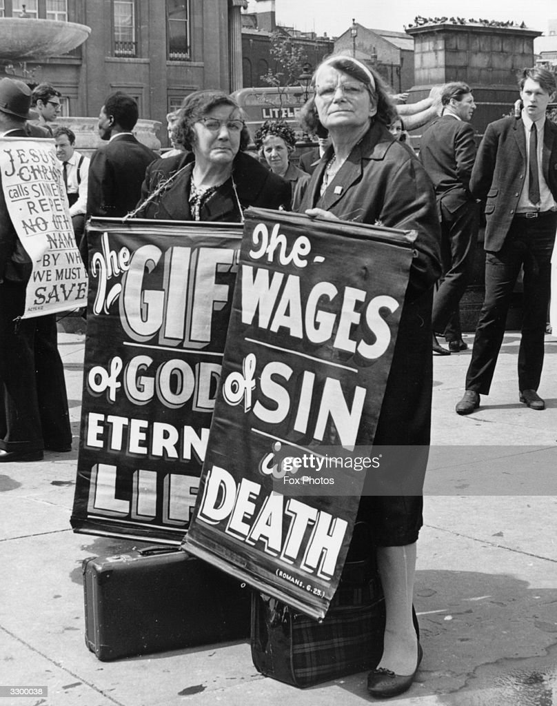 Two women spreading the message at a gospel meeting in Trafalgar Square, London. The slogan reads, 'The wages of sin is death' and ' The gift of God is eternal life'.