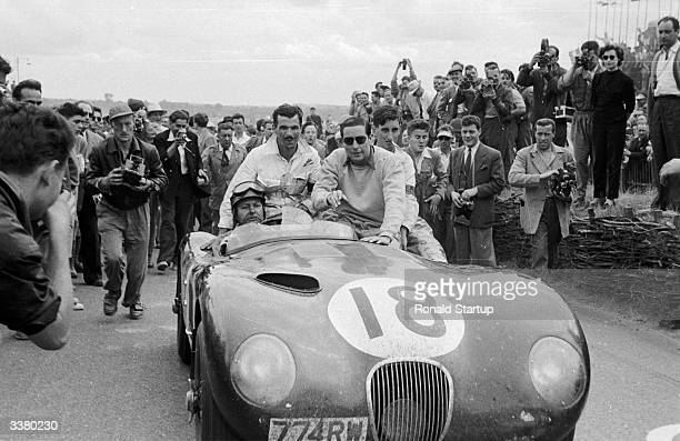 British racing drivers Duncan Hamilton at the wheel and Tony Rolt in glasses drive their winning Jaguar sports car through the crowds after the 1953...