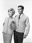An upbeat preppie young couple wear matching woollen Vneck cardigans while being amused by a sight unseen