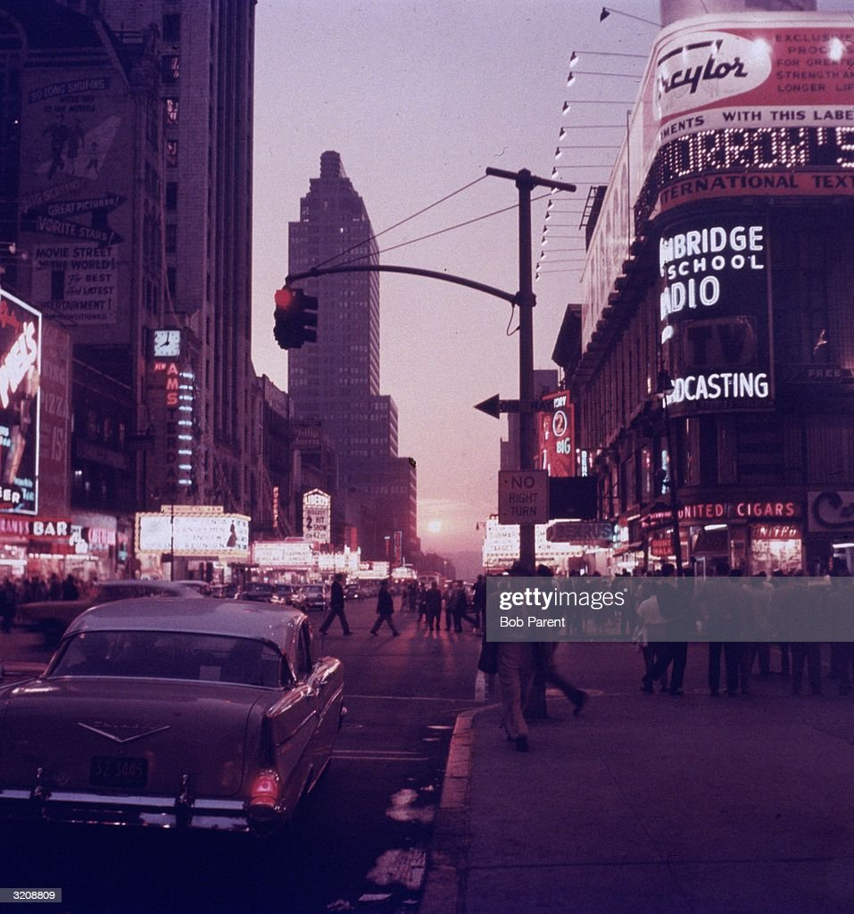 Street scene of Times Square, with neon movie theater marquees and people crossing the street, New York City.